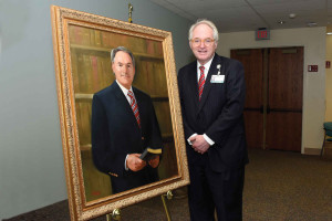 Leod Health President Emeritus Robert L. Colones stands beside a portrait of himself that was unveiled during a ceremony last week at McLeod Regional Medical Center.