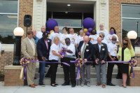 Members of the McClenaghan 100th Year Celebration Committee join Florence One Superintendent Dr. Richard O'Malley, school board members, and city and state officials in cutting a commemorative ribbon during Thursday's ceremony. The renovated former high s