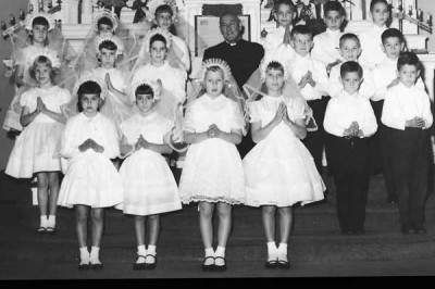 IRST COMMUNION _ A second grade class of St. Anthony's Catholic School poses for a photo celebrating the students' first holy communion in 1964.  with the students is Father Sidney Frances Dean. Do you have an old photo you would like to submit for The Ne