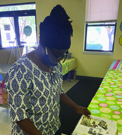 Daphine Tedder looks through a collection of newspaper articles written about the Manna House during her time as its director. Tedder served her final day as director of the non-profit ministry on Friday.